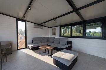 Modern designed living room with luxury sofa and big windows