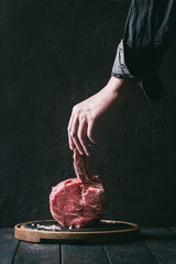 Man's hands holding raw uncooked black angus beef tomahawk steak on bone with salt and pepper on round wooden slate cutting board over dark wooden plank table. Rustic style. Toned image