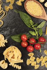 Overhead photo of different types of pasta on black