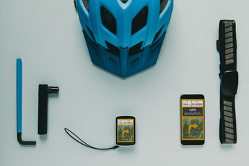 Cycling computer gps, mobile phone and accessories on blue background.