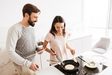 Cheerful young couple cooking pancakes together
