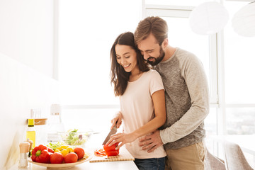 Portrait of a smiling young couple in love cooking