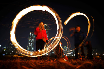 """Participants whirl cans filled with burning wood chips during a celebration ahead of """"Jeongwol Daeboreum"""" (Great Full Moon), which is a traditional Korean holiday that celebrates the first full moon of the lunar calendar, at a park in Seoul"""