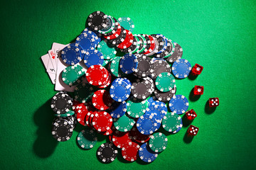 Chips for poker and dices on green table in casino