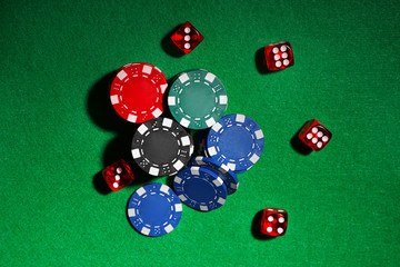 Chips and dices on green table in casino