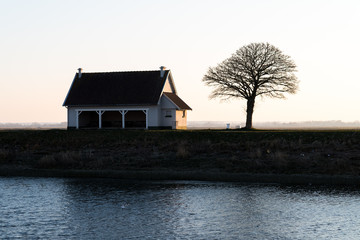 Morning sunrise Backlight behind winter trees and little house by the shore