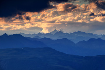Jagged blue ridge silhouettes, snowcapped Rotspitze Pizzo Rosso peak and fluffy orange clouds at sunset, Venediger Group and Villgraten Mountains Defereggen Alps Hohe Tauern Osttirol Austria Europe