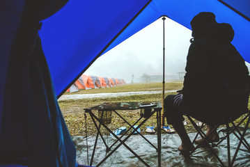 Asian man travel relax in the holiday. camping on the Mountain. sit relax on the chair. In the atmosphere rain fall have fog down. Thailand