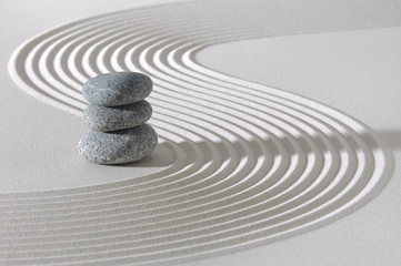 Japanese ZEN garden with stacked rocks in white textured sand