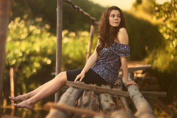 Summer mood concept. Attractive young adult Caucasian girl with long brown hair resting on an old small wooden bridge in the countryside, nature. Barefoot, without shoes. Morning light, warm toning.