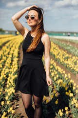 beauty young woman in sunglasses in black dress in tulips field garden