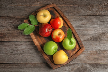Tray with ripe juicy apples on wooden table, top view