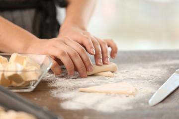 Woman preparing croissants in kitchen, closeup