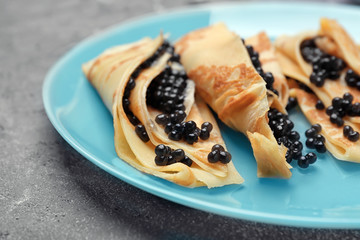 Thin pancakes with delicious black caviar on plate