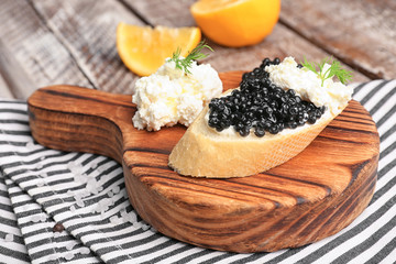 Sandwich with delicious black caviar and cottage cheese on wooden board