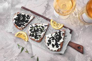 Sandwiches with delicious black caviar on wooden board