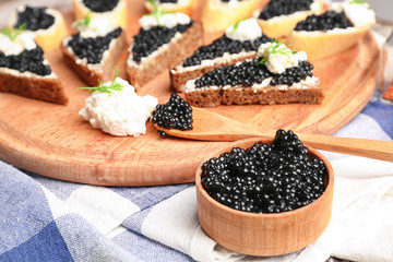 Delicious black caviar and sandwiches on table