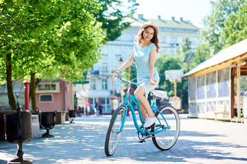 The lady on the retro bike mysteriously looks at the camera on the street of the summer city. The girl is dressed in a blue dress and hat on her head. Retro bike in blue color