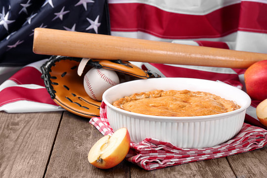 Delicious American apple pie with baseball equipment on table against flag