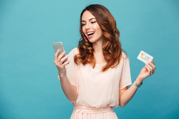 Excited young lady using mobile phone holding credit card.