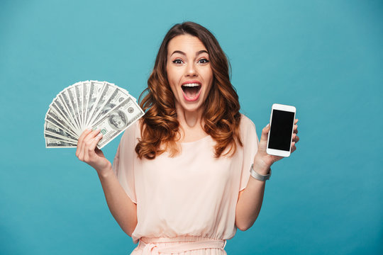 Excited young lady showing display of mobile phone holding money.