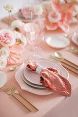 Festive table decor. In pastel pink colors with golden cutlery. With different natural colors roses, peonies, anthurium. Luxury wedding, party, birthday. View from above
