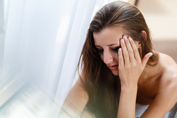 Girl with blurred makeup tears crying in the corner. Depression and stress woman portrait. Broken heart woman crying alone near the window, the concept of Valentine's Day.