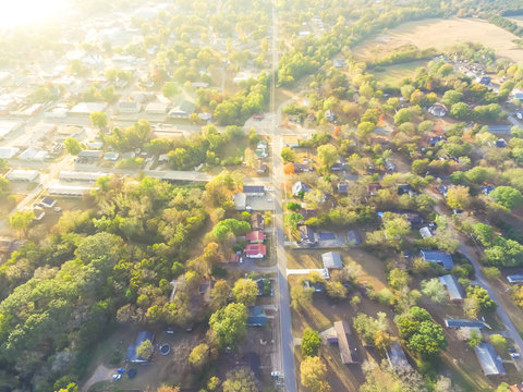 Scenic aerial green suburban area of Ozark, Arkansas, USA. Top overhead residential neighborhood tightly packed homes, driveway surrounded by lush tree flyover in autumn sunset. View from East side