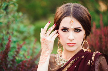 Portrait of beautiful indian girl. Young hindu woman model with tatoo mehndi and kundan jewelry. Traditional Indian costume saree.