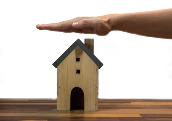 Hands protecting house model on table, real estate