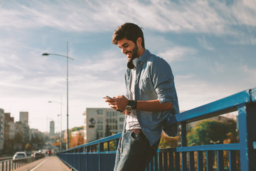 Young happy man using a smartphone  in the city