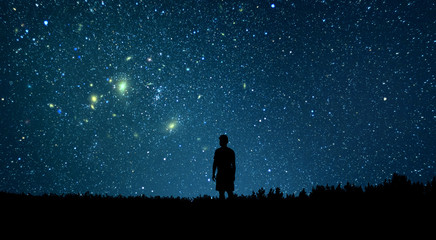 Man looking at the stars. Alone man looking at starry sky. Night sky. Wall mural