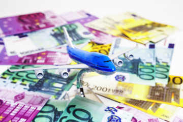 Blue white airplane on dollar and euro in cash close-up. Financial concept. tourist concept.