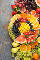 Assortment of cut fruits in rainbow colours oranges grapes mango strawberries kiwis blueberries grapefruit on the grey concrete table, top view, copy space, selective focus