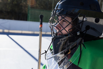 Side view of woman in uniform standing on in-line hockey playground.