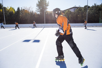 Unrecognizable people riding roller skates while playing in-line hockey in sunny day.