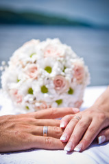 Bridal bouquet and hands of the bride and groom
