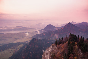 Fotobehang Lichtroze Fantastic mountain landscape, surreal pink and purple sky, the mountains are covered with trees