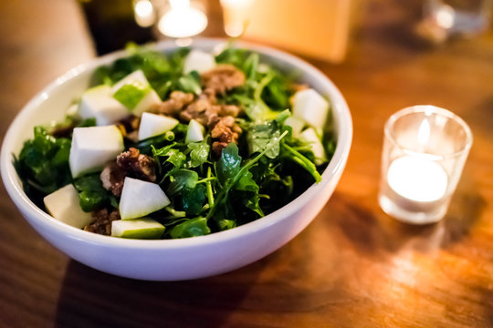 Macro closeup of arugula apple green vegan vegetarian salad in restaurant with candied nuts, walnuts, on wooden table in evening dinner
