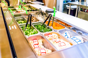 Restaurant buffet serving counter with salad vegetables, celery, kale, carrots, sprouts