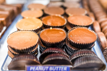 Macro closeup of chocolate peanut butter cups bars candy sweet dessert treats with sign on tray display in store, shop, bakery, cafe