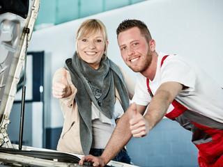 Automechaniker und Kunden zeigen Daumen hoch