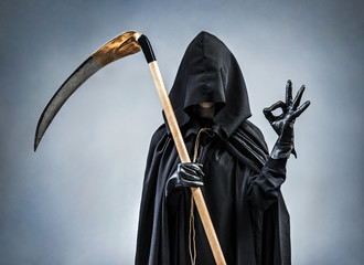 Grim Reaper showing okay gesture. Photo of personification of death wielding a large scythe in silhouette.