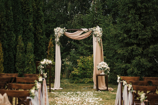 Very beautiful outside ceremony. classical wedding in forest. The arch is wooden. White flowers. Brown chairs. Rite. Bride and groom. Decor. Floristics. In the open air. Path from the petals of roses.