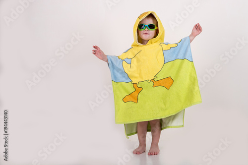 9a710ce308 A happy child in swimming glasses and a bathrobe after swimming in ...