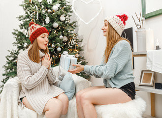 happy girl friends exchanging presents in christmas decorated living room in funny knitted hats