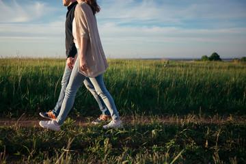Loving boyfriend with a girlfriend walking on road in a green field, holding hands