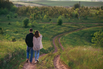 Loving boyfriend with a girlfriend walking along a road that descends from a hill in a green field, holding hands
