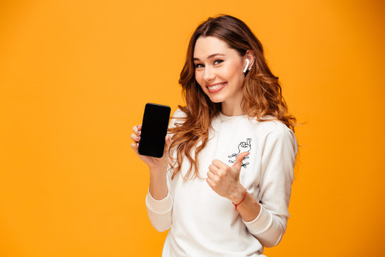 Emotional young woman listening music showing mobile phone