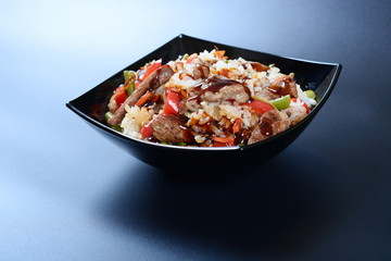 Meat with rice and vegetables in a dark plate